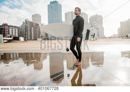 Young Surfer Standing In The Ocean With