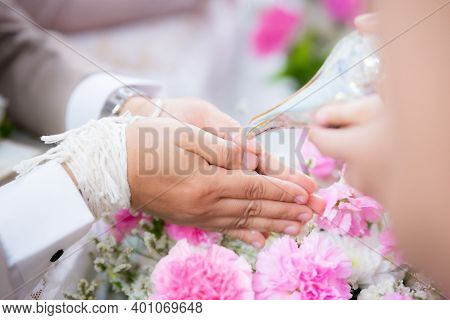 Water Pouring In To Bless The Bride And Groom In A Thai Wedding Ceremony. The Groom's Hands Are Rest
