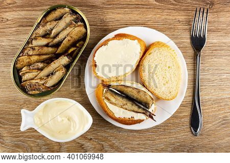 Opened Metallic Jar With Sprats, Bowl With Mayonnaise, Slice Of Wheat Bread With Mayonnaise, Sandwic