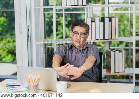 Asian Businessman Tired Overworked He Stretch Oneself On The Desk. Senior Man With Eyeglasses Break
