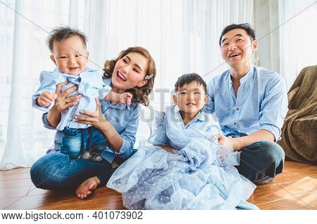 Happy Asian Family Smile And Laugh Together In Living Room At Home. Two Parents And Two Children Kid