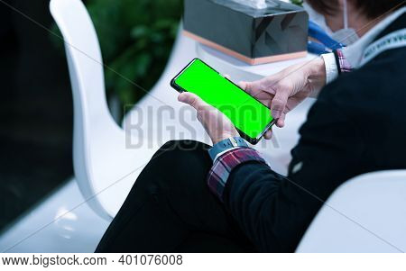 Asian Person Hand Holding Smartphone With Empty Touchscreen Display. People Sit And Using Mobile Pho
