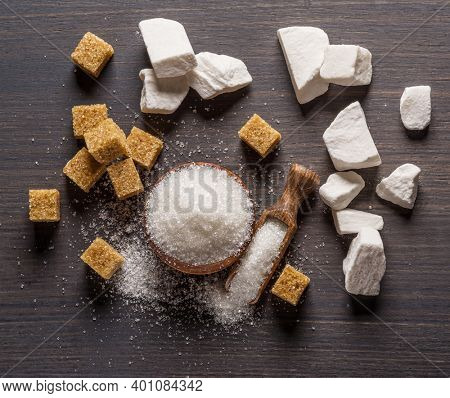Granulated table sugar in wooden bowl and in the spoon and sugar cubes around it on the table. Top view.