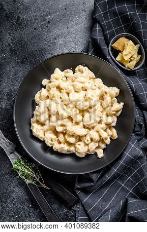 Mac And Cheese. American Style Macaroni Pasta In Cheesy Sauce. Black Wooden Background. Top View