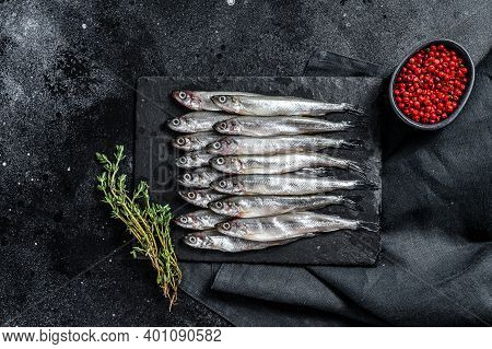 Raw Smelt With Pepper And Thyme. Black Background. Top View