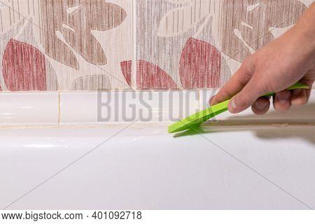 Removing Old Dirty Silicone From Bathtub In A Washroom