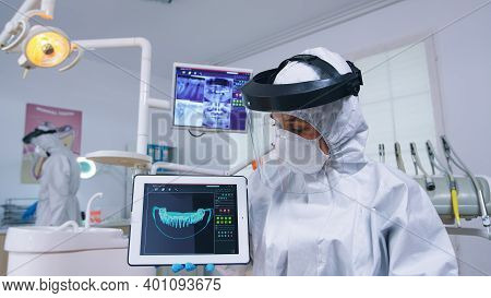 Patient Pov Listening Explication For Teeth Treatment, Dentist In Coverall Showing X-ray On Tablet.