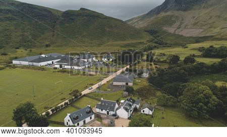 Arran whiskey distillery aerial. Road in green mountains valley. Scottish village with cottages, houses, camp. Rural landscape of coutryside street at summer. Cinematic Scotland alcohol industy shot