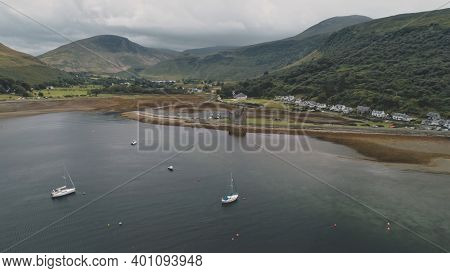 Yachts, ships, boats at Scotland ocean aerial. Seascape of sea bayAmazing nobody nature landscape at summer cloudy day. Cinematic cruise scenery at Arran Island, United Kingdom, Europe