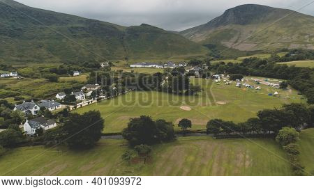 Whiskey distillery at mountain green valley. Nobody nature landscape at summer cloudy day. Scottish village cottages, houses at road aerial. High mounts of Arran Island, Scotland. Cinematic shot