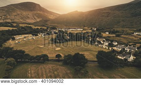 Sunset aerial at village mountain . Nobody nature landscape at sun set. Cottages, houses at road. Whiskey distillery at valley. Cinematic Loch-Ranza, Arran island, Scotland, United Kingdom, Europe