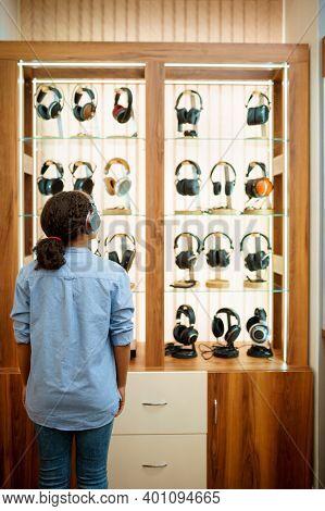 Woman choosing headphones in acoustics store