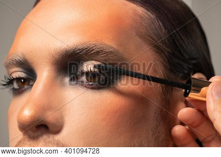 Contemporary makeup artist with black mascara going to apply it on eyelashes of male fashion model sitting in front of camera in studio