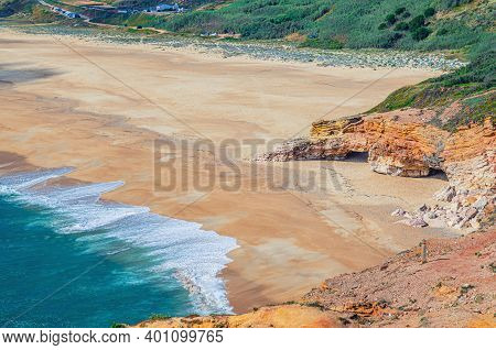 Top Aerial View Of Sandy Beach With Rocks And Cliffs And Waves Of Azure Turquoise Water Of Atlantic