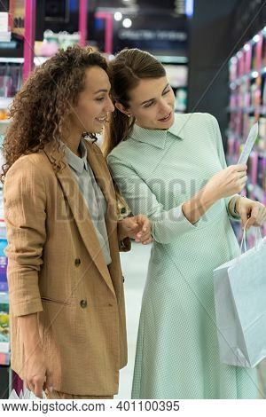 Two young elegant women with paperbags reading information about facial mask while standing in front of large display with beauty products