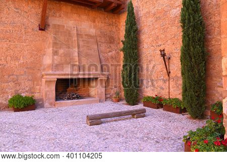 Parade Ground With Fireplace, Wooden Bench, Cypress Trees And Flower Boxes. Belmonte Medieval Castle