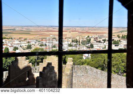 Belmonte Village Through The Bars Of A Castle Window.