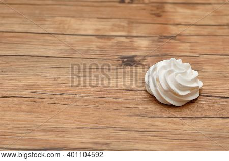 A White Meringue On A Wooden Table
