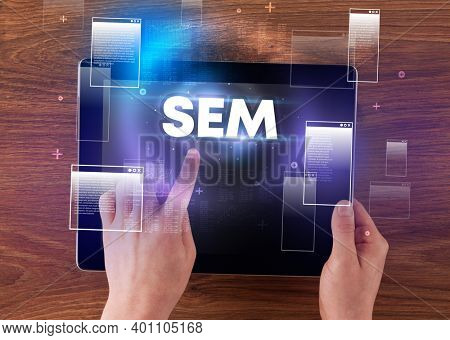 Close-up of a hand holding tablet with SEM abbreviation, modern technology concept