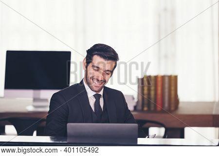 Portrait Of Happy Businessman Sitting At Office Desk