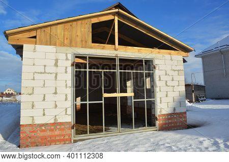 Garage Door Construction Frame.a Car Brick Garage Under Construction With Unfinished Roof, Brick Wal
