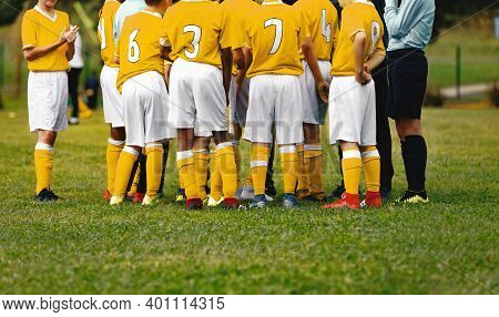 Happy Boysin Yellow Shirts In Sports Team Huddling With Young Coach. Kids Standing In A Circle On Gr