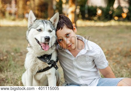 Selective Focus On Husky Dog. Blurred Happy Kid Cuddling Puppy. Portrait Of Boy Is Walking With Dog.