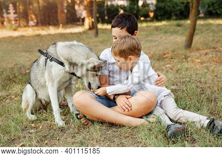 Young Cheerful Kids Resting At The Garden. Children Playing With His Puppy In The Park. Two Boys Sit