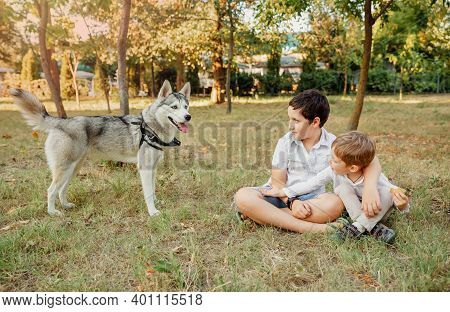 Little Boys Lovingly Hugging His Pet Dog. Cute Children With Dog Walking In The Park On Sunny Summer