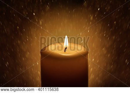 White Candle On Dark Background With Golden Bokeh. The Candle Flame Illuminates The Space Around Her