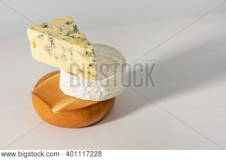 Smoked Cheese, Brie And Mouldy Cheese Are Stacked On Top Of Each Other. Set Of Various Cheeses On Wh