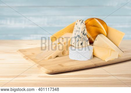 Composition Of Different Types Of Cheese On Wooden Background. Blue Cheese Dorblu, Smoked Suluguni,