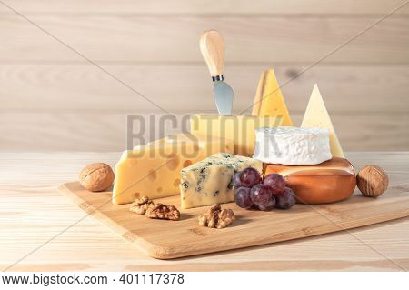 Composition Of Different Types Of Cheese With Walnuts And Grapes On Wooden Background. Blue Cheese D