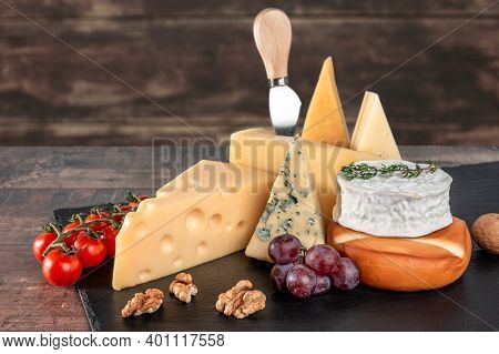Different Types Cheese With Walnuts And Grapes On Black Slate Board On Rustic Wooden Background. Blu