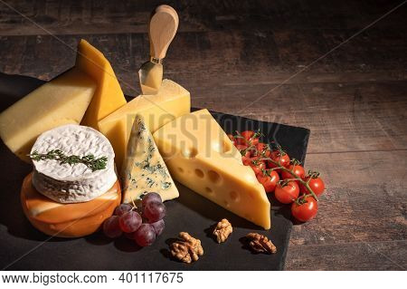 Various Types Of Cheese On Rustic Wooden Table. Cheese Plate: Parmesan, Cheddar, Gouda, Camembert, B