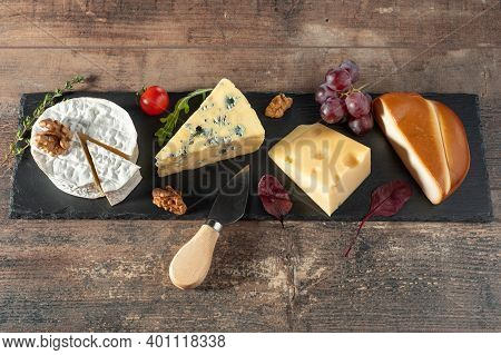 Different Cheeses Laid Out On Long Black Stone Board. Blue Cheese Dorblu, Smoked Suluguni, Brie, Maa