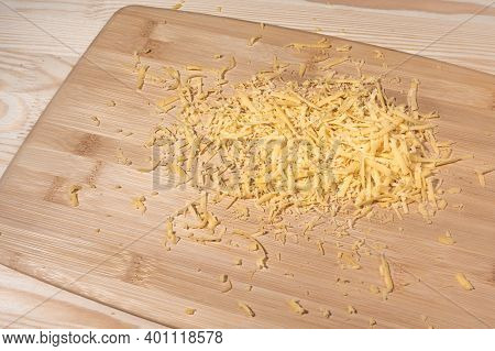 Grated Cheese On A Wooden Cutting Board. Grated Cheese On The Table. Pile Of Grated Cheddar Cheese