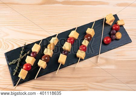 Finger Food. Slices Of Cheese And Tomatoes On A Skewer. Italian Appetizer Skewers With Cheese, Cherr