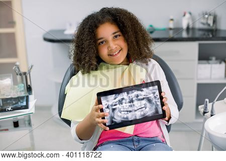 Little Smiling Mixed Raced Girl With Curly Hair Sitting In Dental Chair And Looking At Camera, While