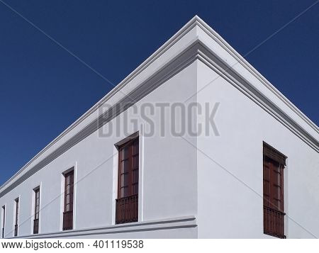 Colonial Building Corner With White Walls, Wooden Windows Under A Deep Blue Sky. Corner Architecture