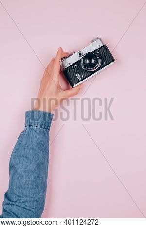 Female Hand Holding Old Retro Photo Camera On Pink Background With Copy Space For Text. Trendy Vinta