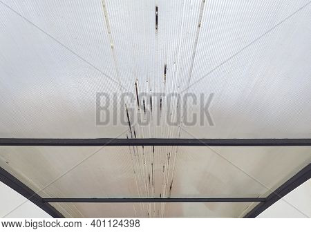 Close-up Of Roof Of Transparent Corrugated Plastic Sheets. Industrial Construction. White Rusty Coat