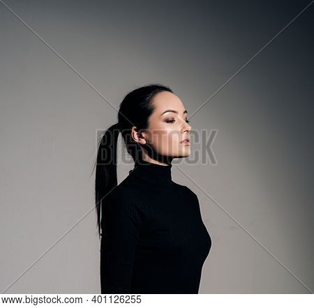 Portrait Of Young Woman In Black Turtleneck With Hairstyle Tail Against Of Grey Background. Side Vie