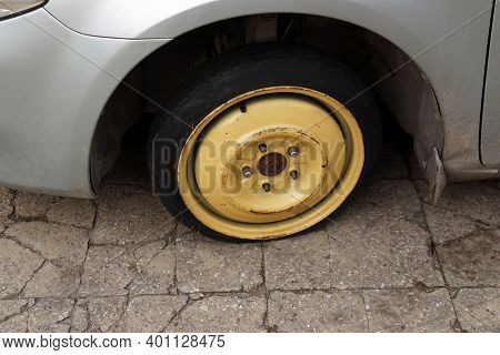 Punctured Old Deflated Car Wheel Close Up.