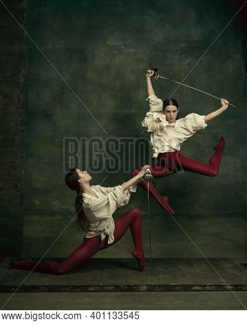 Fight. Two Young Female Ballet Dancers Like Duelists With Swords On Dark Green Background. Caucasian