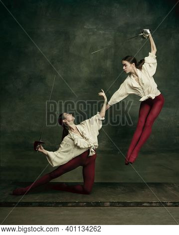 Motion. Two Young Female Ballet Dancers Like Duelists With Swords On Dark Green Background. Caucasia