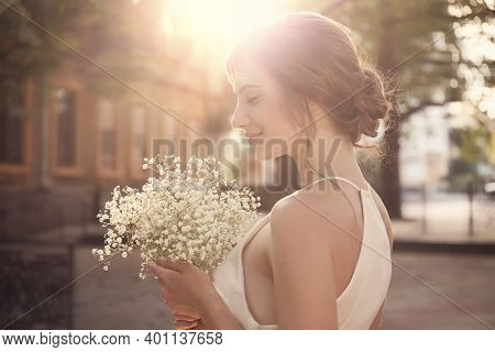 Gorgeous Bride In Beautiful Wedding Dress With Bouquet Outdoors