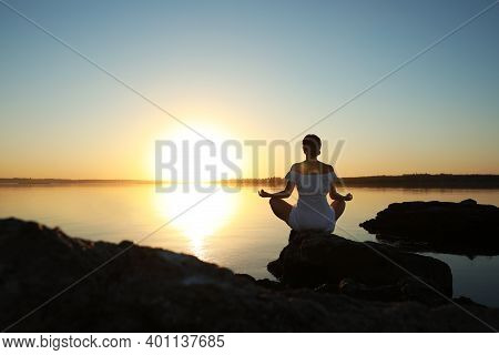 Woman Practicing Yoga Near River On Sunset. Healing Concept