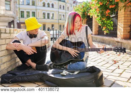 Couple Of Teenage Hipsters Street Musicians Making Money By Music, Girl With Colored Hair Singing An