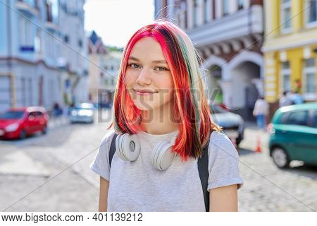 Fashionable Beautiful Girl Teenager 16, 17 Years Old In Wireless Headphones With Bright Dyed Colored